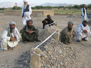 Villagers sit near the graves of victims of air strikes in the Garni, in western Farah province.