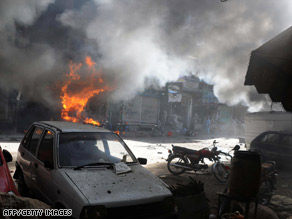 Smoke billows from a fire at the site of a marketplace bomb in Peshawar, Pakistan, on Thursday.