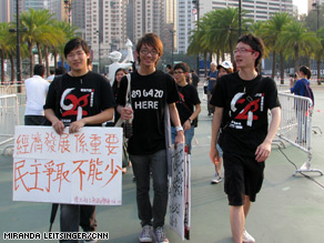 Students hold signs calling for democracy in China and better education aboutTiananmen in Hong Kong.