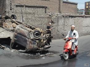 A Muslim motorcyclist drives by a charred car in Urumqi. July 9, 2009.