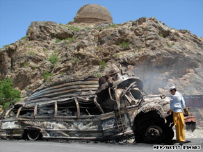 A Pakistani looks at a bus set on fire by Taliban militants in northwest Pakistan in June.