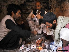 Afghan men smoke heroin in the city of Herat on August 7, 2009.