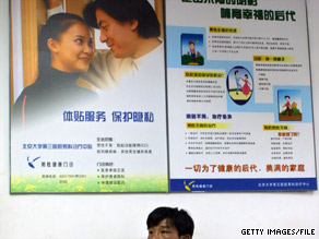 A man sits beneath fertility advertising in Beijing in 2005.