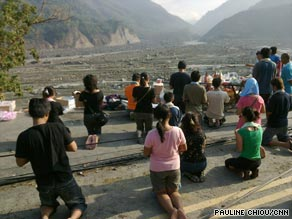 Mourners kneel and pray to the dead as they face the devastated valley of Shiao Lin.