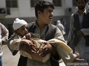 A man carries a child injured in an explosion in Kabul, Afghanistan, on Tuesday.
