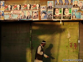 A man walks on a street near electoral posters in Kabul, Afghanistan on Wednesday.