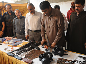 Pakistan security officials show seized weapons and ammunition in Karachi on Sunday after the arrest of seven alleged militants.