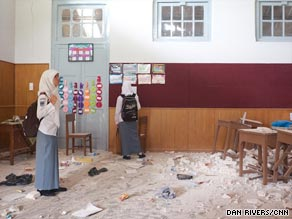 Students inspect their damaged classroom, with tables broken and shards littering the ground.
