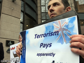 Protesters hold signs outside the Europa Hotel in Belfast before the presentation of the report.