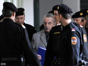 Josef Fritzl is seen without his face covered and surrounded by security guards Tuesday.