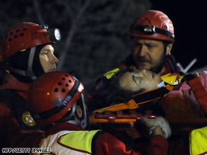 Rescue early Tuesday carry a survivor from the rubble in L'Aquila, Italy.