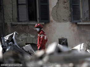 A rescue worker sifts through rubbe on Tuesday in L'Aquila, Italy.