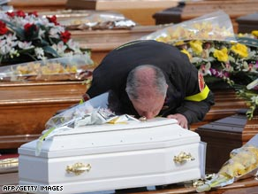 A rescue worker Friday kisses the coffin of a child killed by this week's earthquake in central Italy.