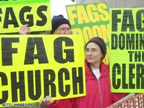 Fred Phelps, obscured, takes part in protesting a New Hampshire church in 2003.