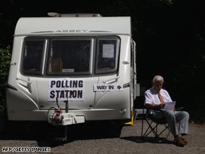 A voting clerk awaits voters outside a voiting station in Salisbury, southern England.