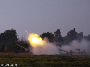Israeli tanks fire shells toward Gaza as evening falls Saturday.