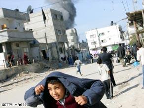 A Palestinian boy runs for cover following an Israeli airstrike Monday in Rafa, in southern Gaza.