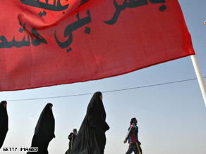 Iraqi Shiite Muslim pilgrims make their way towards the holy southern city of Karbala on Sunday.