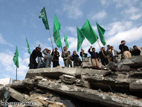Hamas supporters stand on the rubble of a building hit by an Israeli strike.