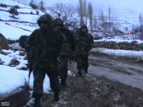 Soldiers tramp through snow and ice as they search for the downed helicopter.