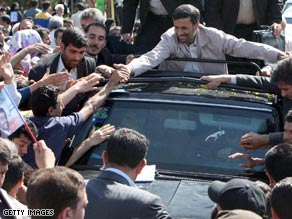 President Mahmoud Ahmadinejad is greeted Wednesday in northern Iran after saying the nation test fired a missile.