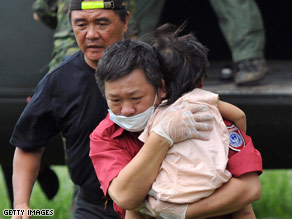 A rescue worker carries a child on Tuesday who survived flooding in southern Taiwan.