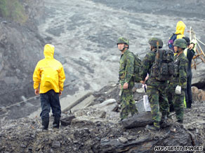 Rescuers and soldiers try to cross a swollen river in Kaohsiung County, Taiwan, on Wednesday.