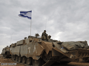 An Israeli soldier sits on his armored personnel carrier Tuesday, after pulling out of Gaza.