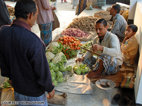 A local man buys food at a marketplace in Bangladesh.