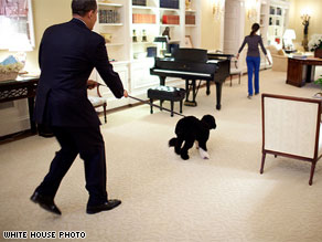 This White House photo, available on Flickr, shows the president walking the first family's dog in the private residence of the executive mansion.