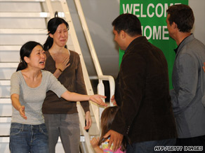 Euna Lee, left, and Laura Ling go to hug their families Wednesday after arriving in California from North Korea.