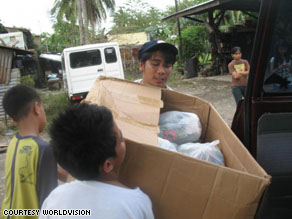 Efren and other volunteers load donated items into a vehicle to begin distributing them to families in need throughout Cavite, Philippines.