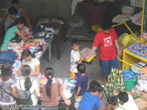 Volunteers with Efren's group, Dynamic Teen Company, sort donated clothes and prepare to distribute them to families in need in Cavite, Philippines.