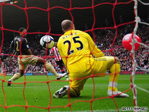 Sunderland striker Darren Bent (obscured) shoots towards goal and the ball hits a beach ball that had been blown onto the pitch.