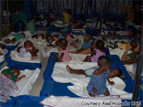 Haitian children sleep outside under a shelter with nannies of the Real Hope for Haiti rescue center.