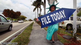Craig Baldwin holds a sign advertising a tax preparation office for people that still need help completing their taxes before the Internal Revenue Service deadline on April 14, 2010 in Miami, Florida.