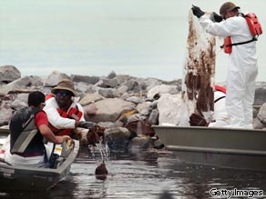Oil cleanup workers try to remove thick oil that washed ashore on July 1, 2010 in Gulfport, Mississippi.