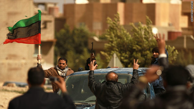 An internal security officer waves the old national flag Thursday in Libya's rebellious city of Tobruk.