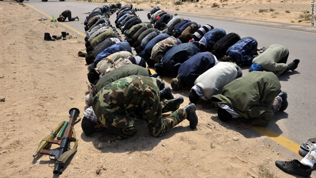 Libyan rebels pray while preparing for battle against government forces near the city of Ajdabiya.