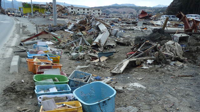 Hundreds of photos sit in baskets by the side of the road in the destroyed Japanese town of Minamisanriku.