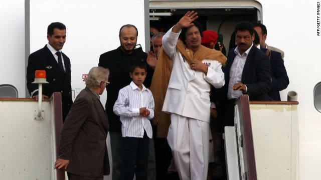 Gadhafi exits a plane in Tripoli with family members and bodyguards after traveling to the United States and Venezuela in 2009.
