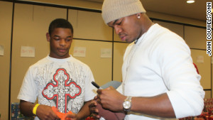 Ne-Yo signs a football for Tha Banks, 16, who is in foster care.
