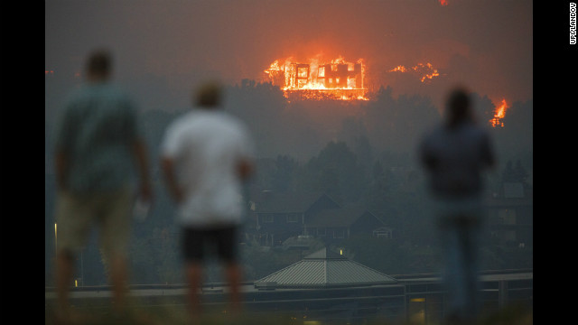Residents of Colorado Springs watch as the Waldo Canyon Fire burns a home in the Mountain Shadows neighborhood on Tuesday.