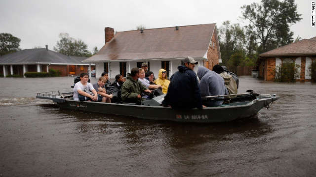 Rescue workers transport residents trapped by rising water from Tropical Storm Isaac in LaPlace, Louisiana, on Wednesday, August 29. While Isaac lost its hurricane status, officials warned of continued threats from storm surges and flooding.