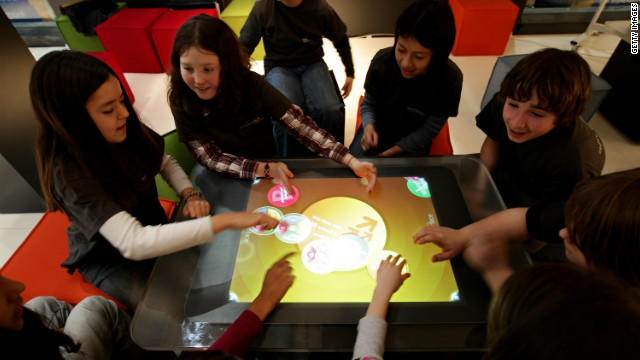 a group of the Plural generation, digital natives, share a common touchscreen and play in the virtual world
