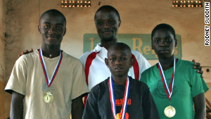 Robert Katende (center, rear) and Phiona Mutesi (right) after the 2009 International Children\'s Chess Tournament in Sudan.\n