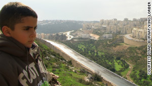 Emad\'s son Gibreel looks over at the Israeli settlements