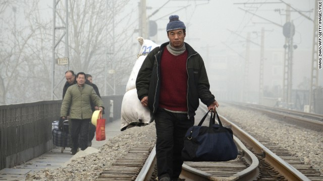This picture taken on January 12, 2013 shows a Chinese migrant worker walking with his baggage along a railway line in Beijing.