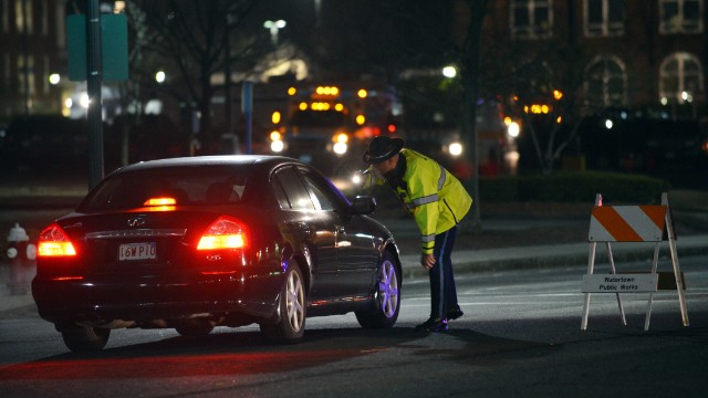 A police officer talks to a driver at a checkpoint in Watertown, Massachusetts.