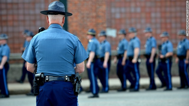 A Massachusetts state trooper watches other troopers line up at Watertown Mall as the manhunt for the second suspect continues in Watertown on Friday.